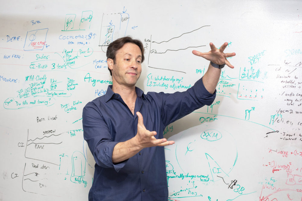 A photo of David Eagleman making hand gestures in front of a whiteboard covered in writing