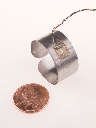 A silver-colored ring with multi-colored wires attached, next to a penny for scale.