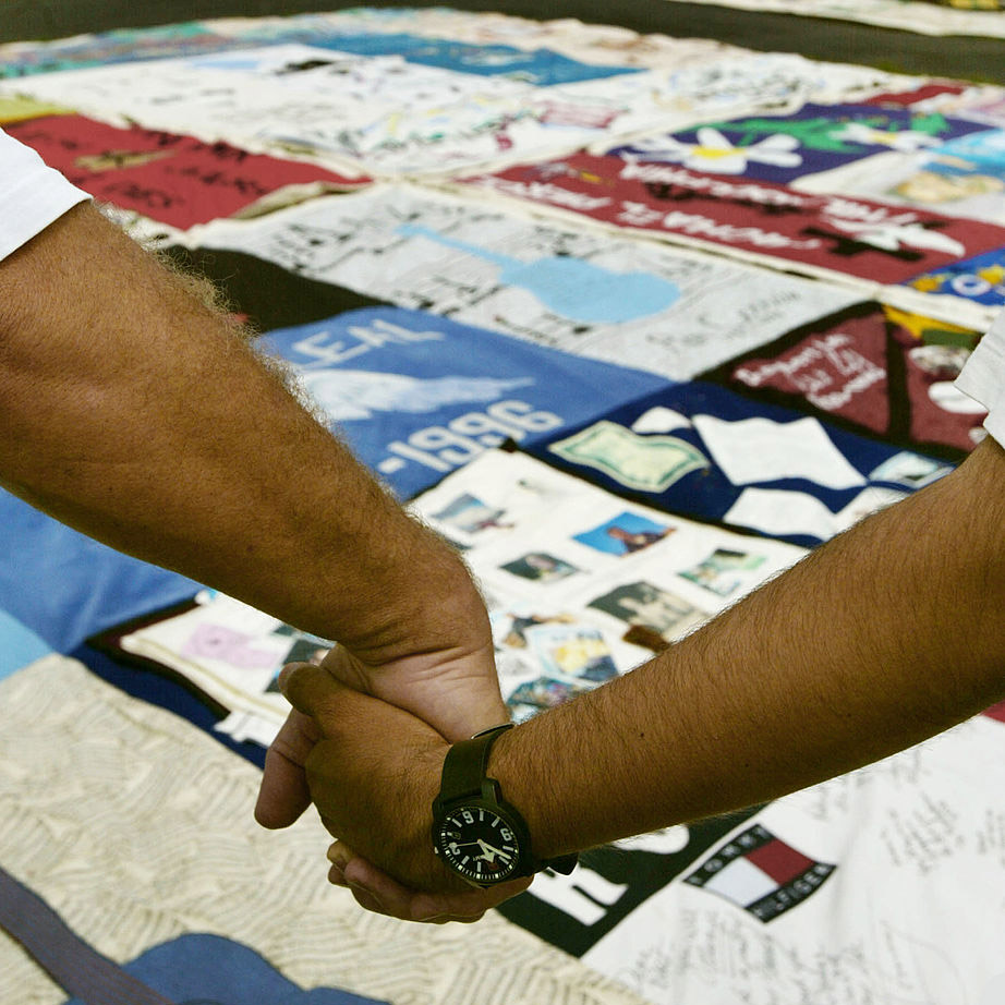 People hold hands while standing at the AIDS Memorial Quilt June 25, 2004 in Washington, DC.