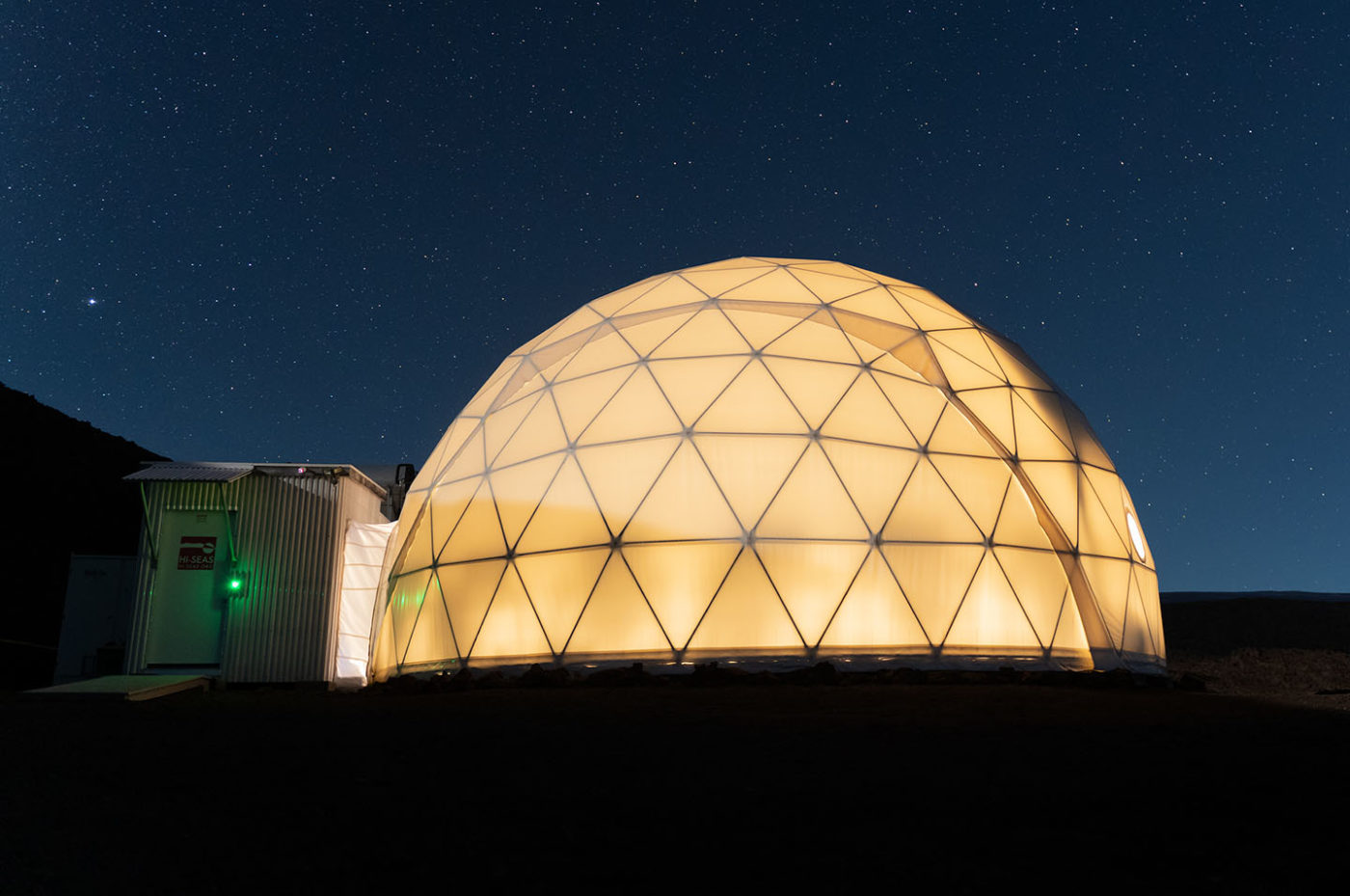 A photograph of a large dome glowing at night.