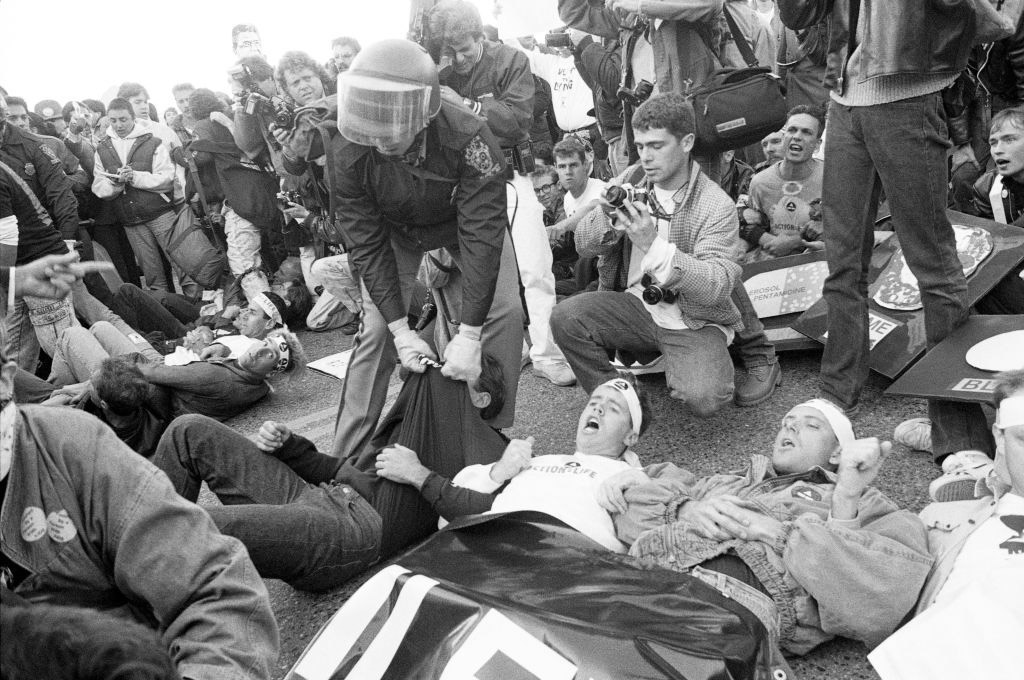 A photograph of a police officer and ACT UP protesters at the FDA headquarters in 1988.